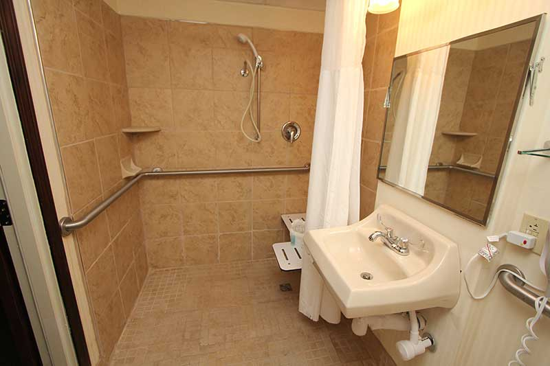 Accessible bathroom shower and sink in hotel room at Black Bear Inn & Suites in Gatlinburg TN