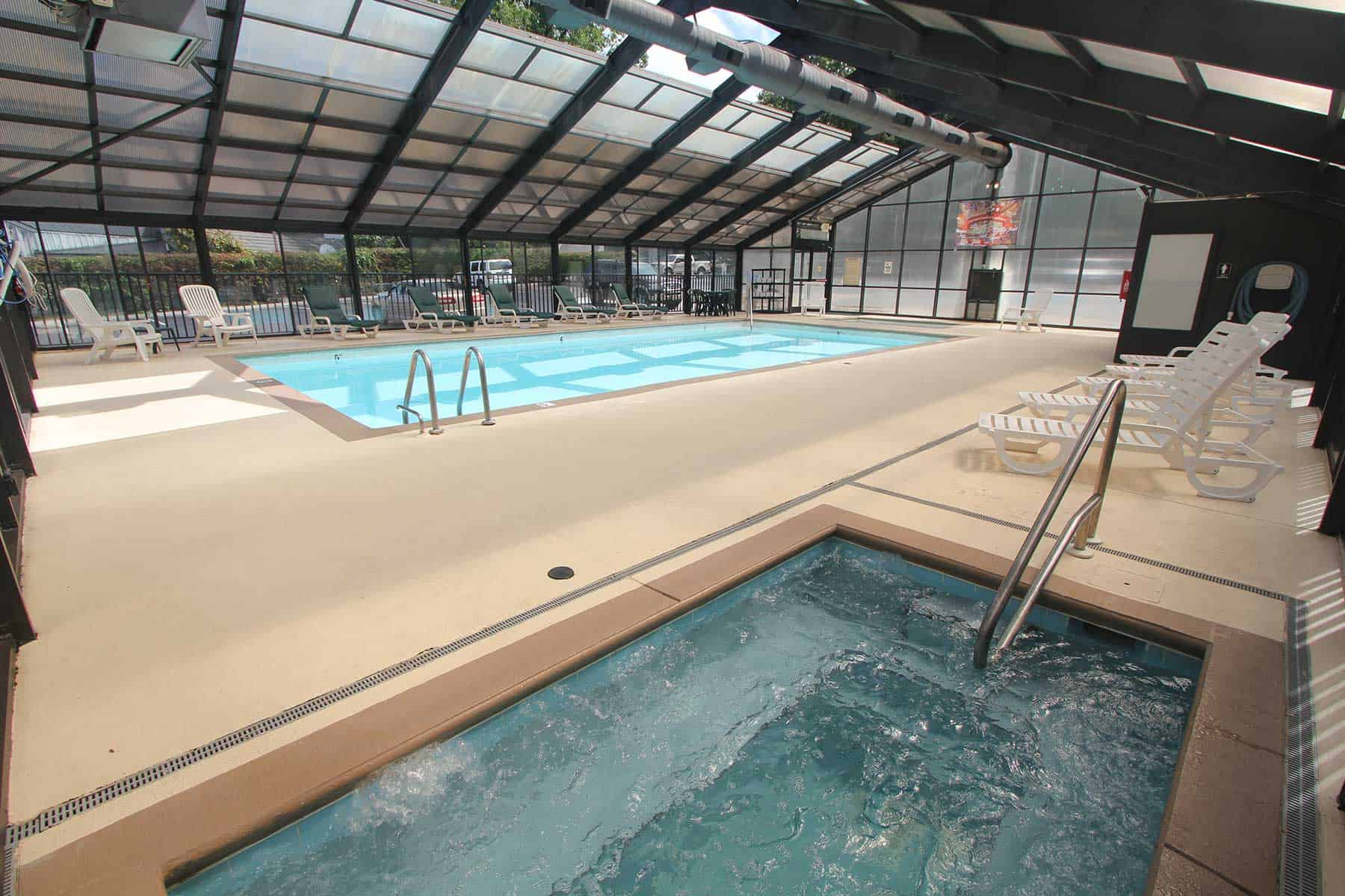 enclosed heated pool with hot tub and lounge chairs