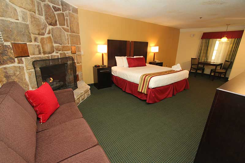 Hotel room with king bed sofa and fireplace at Black Bear Inn & Suites in Gatlinburg TN