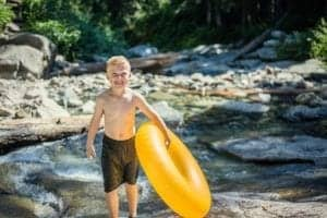 little boy on the river holding a yellow inner tube