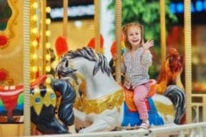 little girl riding the carousel